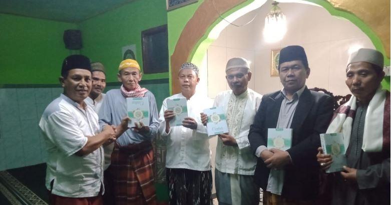 Kepala desa Sekarwangi Ridwannulloh S.Sos membagikan kitab Al -Quran di mesjid Al-Fatwa
